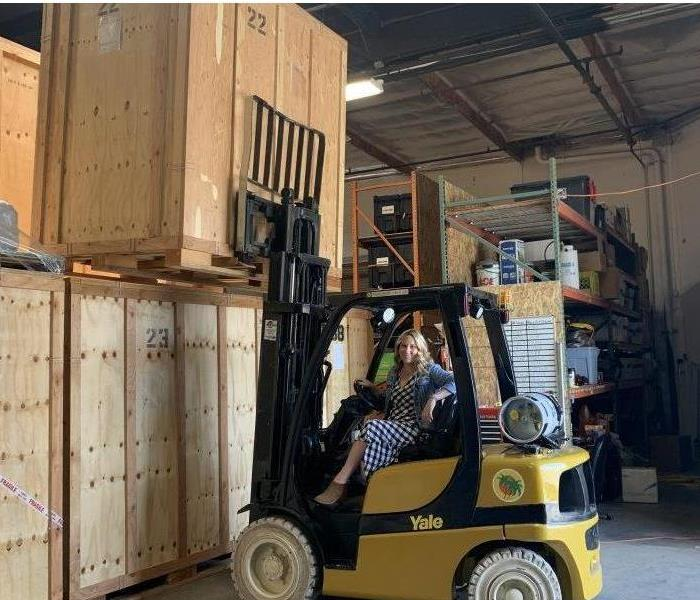 A photo of a woman on a forklift.